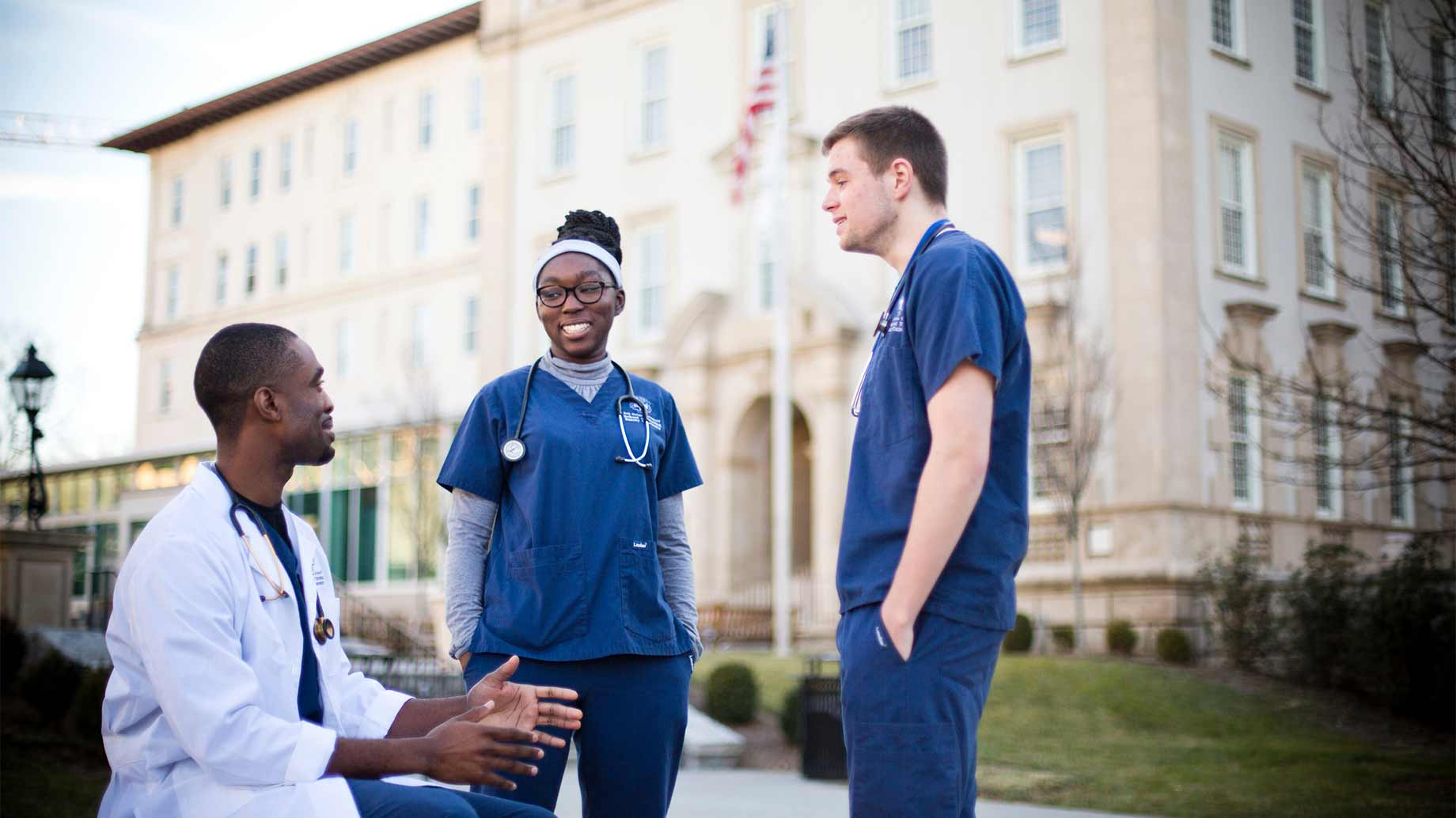 two nursing students and a medical student chatting in front of a medical school building