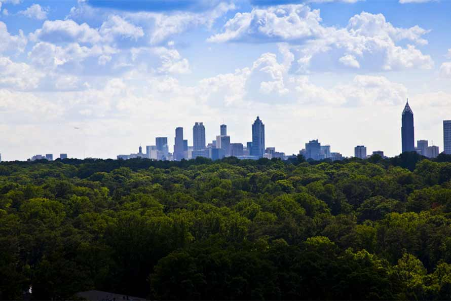 Cloudy blue skies with green treetops and Atlanta skyline in the distance