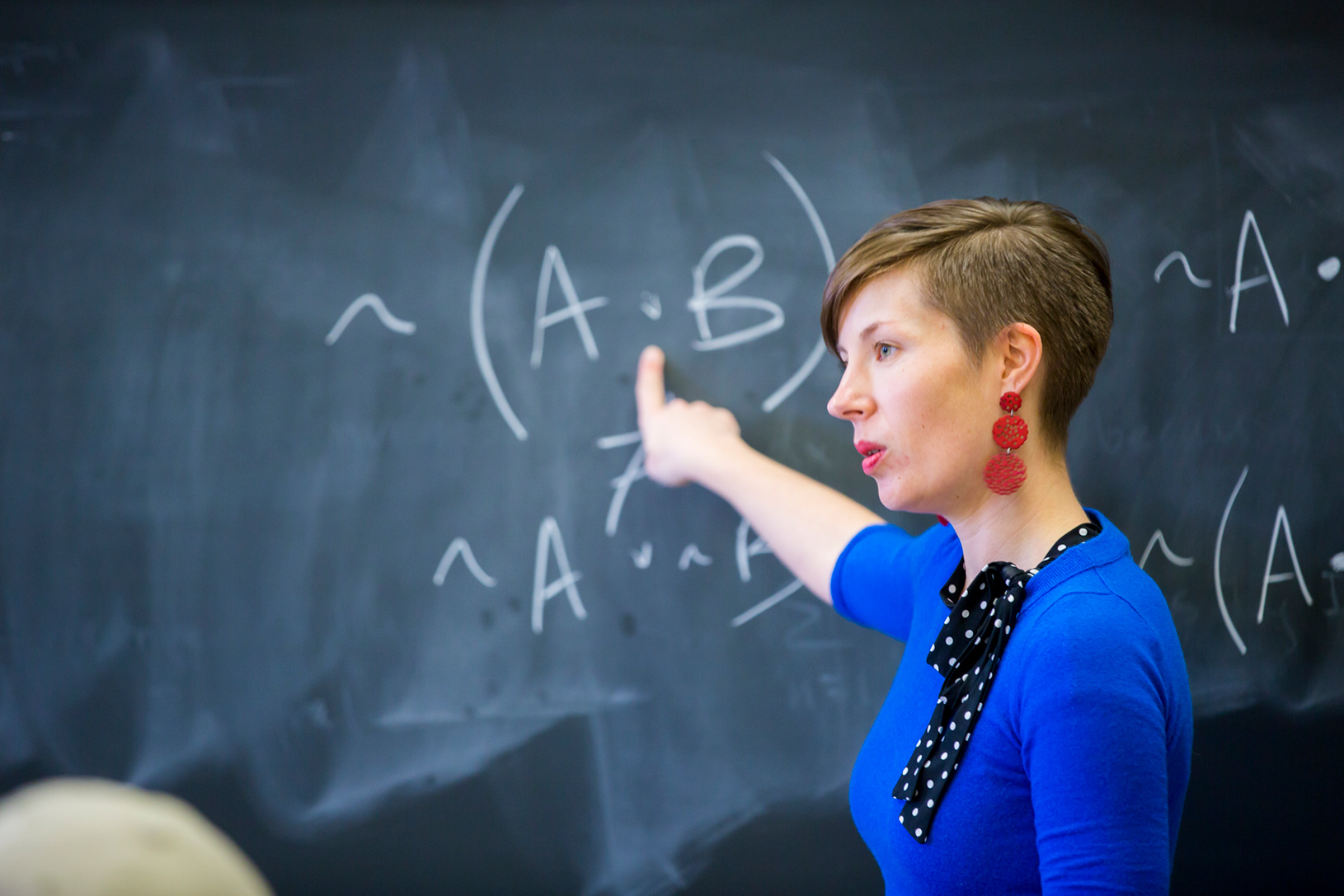 Oxford female professor in bright blue dress pointing to blackboard