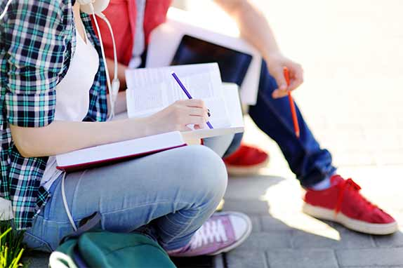 girl in plaid shirt writing in notebook with boy in red shirt and sneakers beside her